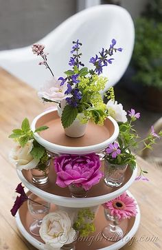 Stacked terracotta pots and fresh flowers form a lovely, quick and easy centerpiece for your garden or wedding table. via http:www.Songbirdblog.com