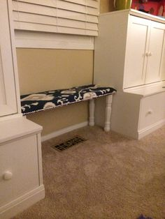 DIY reading bench between toy storage.  Mdf, foam, batting, nailhead trim, and some legs sprayed white from lowes