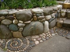 Rock Retaining Wall With Spirals River Rock Retaining Wall With Spirals - thinking this would work with my field stone, too!River Rock Retaining Wall With Spirals - thinking this would work with my field stone, too! Garden Paths, Garden Art, Garden Landscaping, Landscaping Ideas, Garden Edging, Mosaic Garden, Mosaic Walkway, Rock Walkway, Rocks Garden
