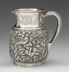 A fine sterling silver repoussé water pitcher thomas f. brogan (active 1896-1930), new york, ny, retailed by theodore b. starr The columnar form body with repoussé birds perched upon and flying amid leafy branches, raspberry canes and cherry bunches, all against a stippled ground, the handle with conforming decoration, monogrammed.
