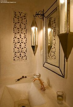 wonderful lights, mirror, carved panel, and sink for an ethnic touch on a bathroom