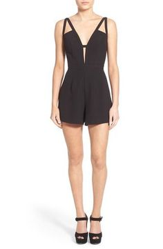 Angular cutouts and a dramatically plunging back add evening-worthy allure to this chic black romper with a revealing V-neckline.