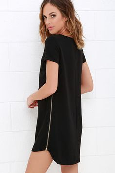 You'll be one step ahead of the game when you sport the New Era Black Shift Dress! Rounded neckline and short sleeves frame a classic shift bodice, made of medium-weight woven poly fabric. Straight-cut silhouette is accented by chic gold zippers along the side seams, adding a notched look to the slight high-low hem.