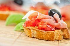 Préparation :  1. Lavez et coupez les tomates en petits dès. Coupez les tranches de jambon ibérique en deux. 2. Pelez la gousse d'ail et dénoyautez les olives. 3. Faites griller les tra…