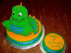 """Dino's 1st Birthday - This dinosaur is made from the Stand-up Cuddly Bear Pan.  Orange candy melts were used to make the spikes.  Dino sits atop a 12"""" round single layer iced smooth with buttercream.  Matching 6"""" round smash cake.  This was a really fun cake to do.  Design came from the Wilton Dinosaur but adjusted the colors to fit theme."""