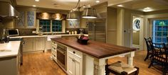 Traditional Kitchen with Heirloom Wood Countertops Black Walnut Plank, Limestone counters, Inset cabinets, Glass panel