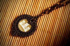Regency bottle cap necklace handmade in Montréal with bronze metal framing.