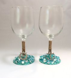 Cheers to our new Sea Breeze Product Line! Enjoy a glass of Chardonnay while daydreaming about the open sea with these Nautical Diamond Wine Glasses. This set of two each comes with an Anchor and a Helm; one on each glass. Theyre designed with intricately placed Aqua Diamonds, Glass Pearls, and a few hints of glitter. Both glasses come with small rope around the stem to embrace the nautical feel. Please remember:  Everything in our shop is handmade, Our products do NOT belong in the dishw...