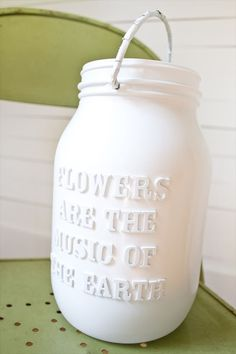 White with Lettering  Wooden letters can be placed on the jar prior to painting to reveal a message after it dries. We love the idea of a custom quote or favorite song verse. Fill with flowers and place a different one at each table.