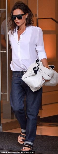 Victoria Beckham sticks to comfy boyfriend jeans and flat sandals...