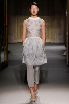 White sheer (organza?) long tunic with gray floral embellishments worn over gray cropped pants. GEORGES HOBEIKA COLLECTION