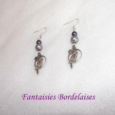 """Boucles d'oreilles """"oiseau"""" en métal argenté et perles grise et bleue  Paire de boucles d'oreilles en métal argenté (sans nickel) avec perroquet perché et petites fleurs, ainsi que deux perles nacrées en verre (bleu foncé et grise).  #boucles #oiseau"""