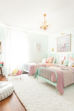 Girls room with twin beds in muted pink and mint tones with Land of Nod (via Lay Baby Lay).