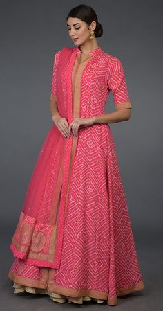 From our Heritage Bridal Collection, this beautiful Fuscia Peshwa Anarkali has handcrafted white-yellow Bandhej and banarasi gold zari weave floral booteh all over with banarasi gold zari weave borders along the front opening, hemline (ghera), an Indian Attire, Indian Wear, Indian Outfits, Anarkali Dress, Lehenga Skirt, Lehenga Blouse, Indian Designer Outfits, Designer Dresses, Bandhani Dress