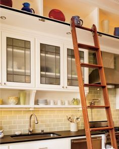 Still wish I could have a library ladder like this but notice the little shelf under the cabinet.  Good way to end the cabinets.