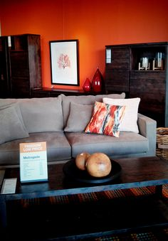 orange wall, dark woods, grey couch, white accessories...