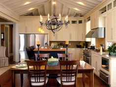 The family room and kitchen share a hipped roof, with an exposed beaded board ceiling and rafters. This type of treatment creates a relaxed setting and continues the louvered cabinets' tropical feel. (Photo: Photo: Jean Allsopp;)