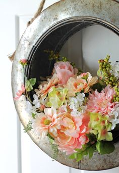 DIY Spring wreath tutorial with a farmhouse repurposed antique style. Learn some great tips for flower arranging and end up with this pretty vintage metal tire wreath. The blush pink flowers are gorgeous!