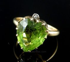 This genuine large Peridot heart ring is set in 9ct yellow gold The ring is all Victorian Circa 1880 The ring is steeped in Victorian history - this is not a reproduction.The central 5ct Peridot has a rich grassy olive green glow set with a sparkling Rose Cut Diamond at the top of the gallery which is set in Silver Peridot is a stone of lightness and beauty,Peridot was believed to be a stone of springtime by ancients who considered it a gift from Mother Nature.