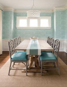 Gray bamboo dining chairs with turquoise blue leather seat cushions flank a trestle dining table and complement an aqua and white table runner illuminated by a white pierced drum pendant.