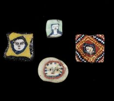 Roman mosaic glass face beads, 1st century B.C.-1st century A.D. Including a small square plaque of pale green glass with a female bust with long black hair, a square plaque in black and yellow glass with central face with fine black details, another red plaque with yellow, black and white chequered pattern and central face and a opaque white disc with face within a red circle, 7mm-12mm long. Private collection