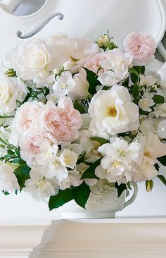 Various varieties of fresh white flowers explode out of a barely visible 18th-century trophy vase with ornate relief. (via floral arrangements by Carolyne Roehm - Style At Home)
