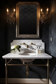 powder room - black walls, antique sconces and mirror.