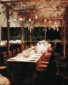 Votive candles illuminated a canopy of grapevine arbor at this formal wedding in the New York Botanical Garden.
