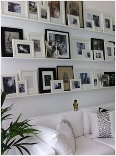 This photo organizing solution is perfect for apartments. You can have the look of a photo collage without 100 nail holes in your wall. Simply hang long narrow shelving units then layer frames by leaning them against the wall. Be sure the shelf is deep enough to hold the photographs without risk of them tipping forward. You can even use some wall-safe tack adhesive putty to give your photos a little extra support.