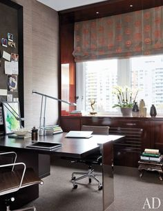 A home office with grass-cloth wall coverings and a silk polka-dot roman shade | archdigest.com