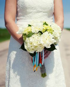 Jessie carries a bouquet of white and mini green hydrangeas and white peonies. Twine and tails of vibrant ribbon add color.