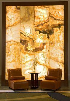 Parte de un muro, recubierto con piedra onix amarillenta. Se utiliza bastante en espacios abiertos para ambientar con luz y que por si sola le de presencia al lugar.