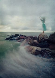 She frees her self by the sea, waves crashing their ancient song, envelope her in their flow.