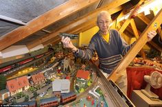 All aboard: Roger Stimpson holds onto a model train above the model railway that he built in his loft