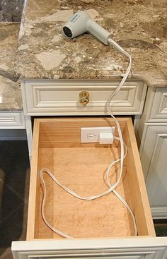 Brilliant! Save your backsplash from unsightly wall outlets! By adding the outlet to the inside of your cabinet, you can keep your hair utensils organized and always powered. This is a cabinet feature to consider in your next bathroom remodel.