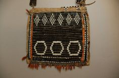 Square pouch or bag constructed of skin and cloth, the front covered with a large panel of loomwoven glass imitation wampum, black ground, white details, with a strap also of imitation glass wampum. The bag face, of 26 horizontal rows of beads on 27 warps, has three white heaxagons at the bottom, and six white diamonds at the top. The sides of the bag are edged in orange quillwork in zig-zag line technique, followed by a row of imitation-wampum, five beads deep, three black in the middle…