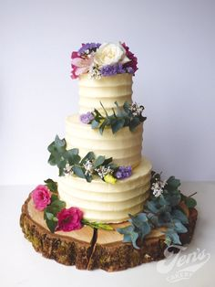 Buttercream covered cake with fresh flowers and eucalyptus.
