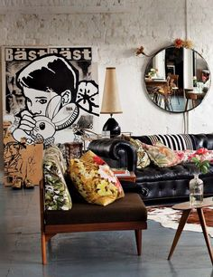 Kitsch living space set in this industrial loft. Gorgeous leather couch, hide rug & vintage pieces.