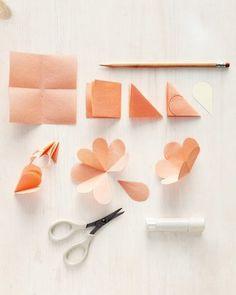①正方形の紙を三角に折りたたみ一片を切り取って、お花をつくっていきます。