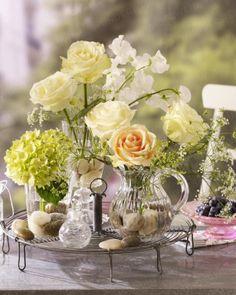 Und so geht´s:  1. Gefäße zu ca. 1/3 mit Kieseln füllen und mit Wasser auffüllen. 2. Die weißen Rosen und Wicken schräg angeschnitten in das höhere Glas stellen. 3. Ammi majus und Hortensie vom Grün befreien und schräg einkürzen. Stiele zur besseren Haltbarkeit kurz ankochen und in die anderen wassergefüllten Gläser verteilen. 4. Die apricotfarbene Rose mit in das Glaskännchen stellen.