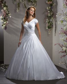 Understated yet elegant in its simplicity, this lovely satin gown features beaded band embellished with crystals for a touch of glamour. The bodice is draped with pleats and the tulip cut sleeves add ease of movement. The full A-line skirt has asymmetrical pleating with discreet side pockets. | Bonny Bliss Bridal: Style 2407 | Modest Wedding Gown