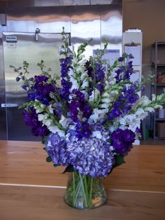 Purple hydrangeas along with purple larkspur, stock and white snapdragons make for a stunning altar arrangement. www.bloomtasticweddings.com