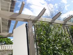 Glass roofed pergola with chinese jasmine trained up the side to create 'walls'