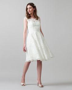 A beautiful tea length embroidered wedding dress with scalloped edging, a semi-sheer yoke and button fastenings at the back. Complete with a detachable grosgrain waistband and a sweetheart neckline at the lining.