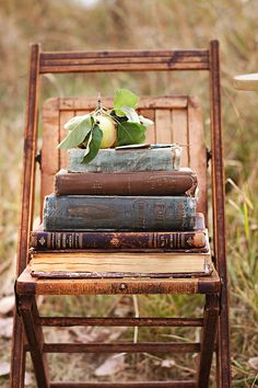 stacked vintage books on a vintage chair.