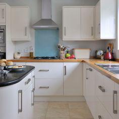 mix of materials glass splashback, wooden countertops, stone floor add depth to all white kitchen