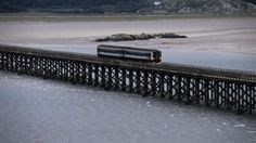 Train crossing the wooden Barmouth railway viaduct, the longest in the UK.