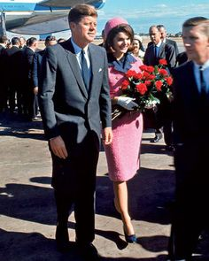 The First Lady received red roses upon their arrival at Dallas Love Field on Friday, November 22, 1963. In one hour, the President would be assassinated.