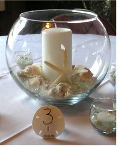 A simple but elegant beach wedding candle and shell centerpiece.