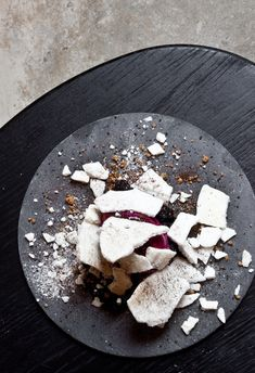 Beet ice cream with compote of blueberries stirred with dried blueberries and caramelized white chocolate sprinkled with meringue of apple vinegar and raw licorice. Served on New Norm Dinnerware slate